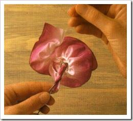 2. Используя узел как центр цветка, оберните вокруг его основания собранный в складки край ленты.